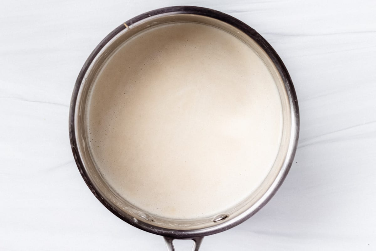 Melted cheese with seasonings and beer in a silver saucepan