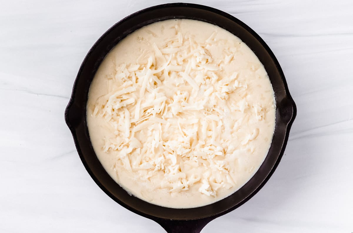 Beer cheese dip in a cast iron skillet topped with shredded cheese before broiling