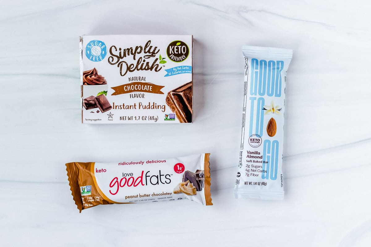 Keto pudding box and 2 keto bars on a white background