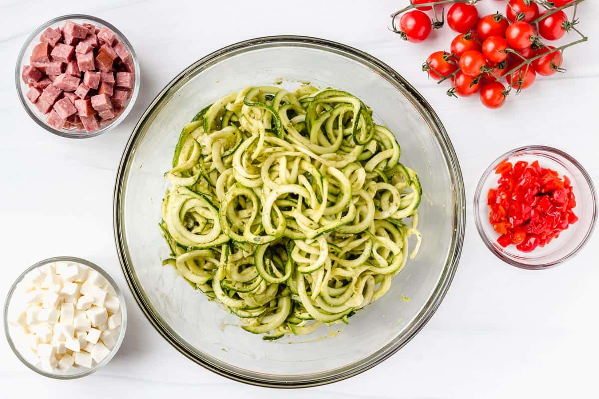 A bowl of zucchini noodles with pesto mixes in them and other ingredients for the salad around it