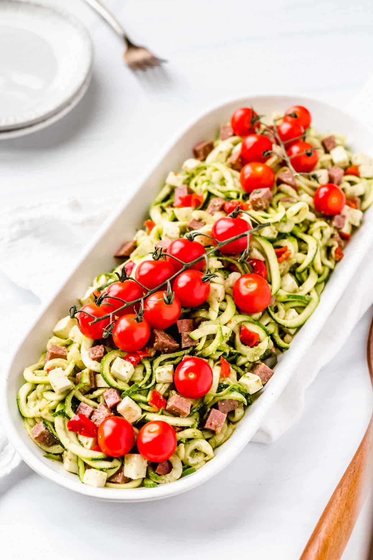 Zucchini Pesto Pasta Salad in an oval serving dish on a white background with 2 white plates and a small fork behind it