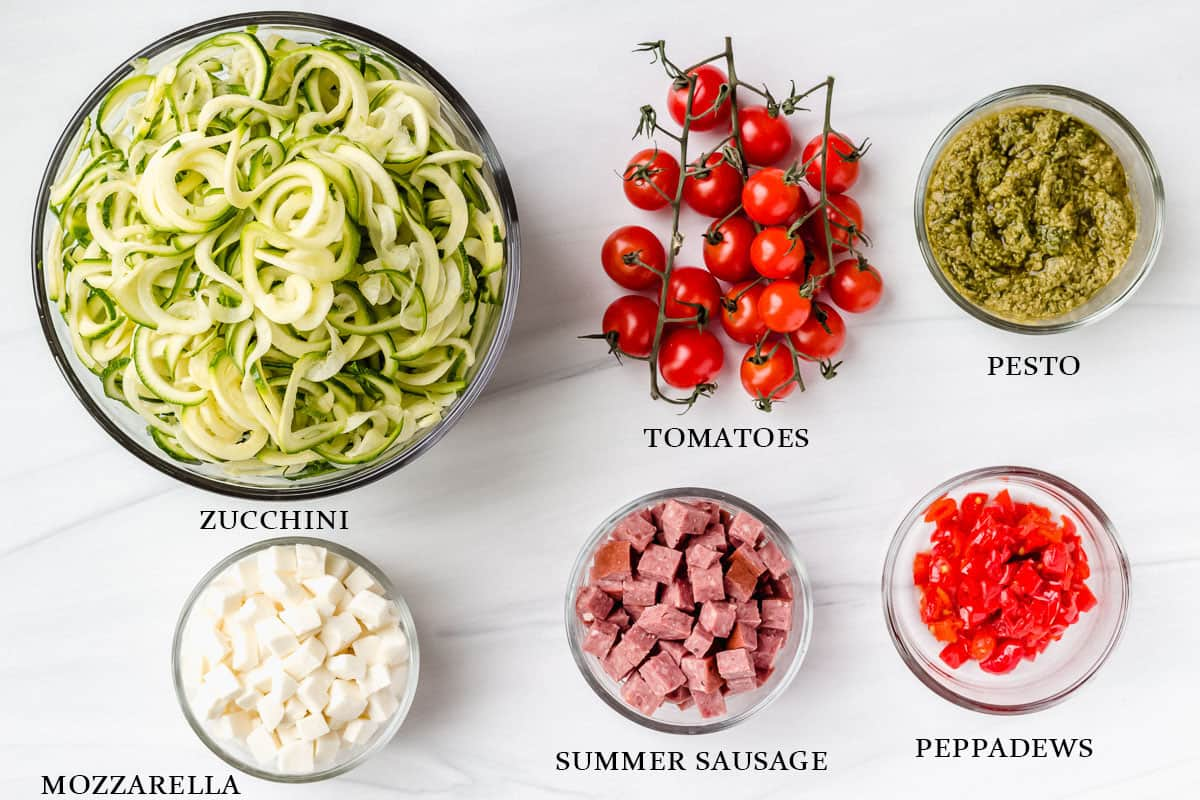 Ingredients to make zucchini pesto pasta salad with labels on a white background