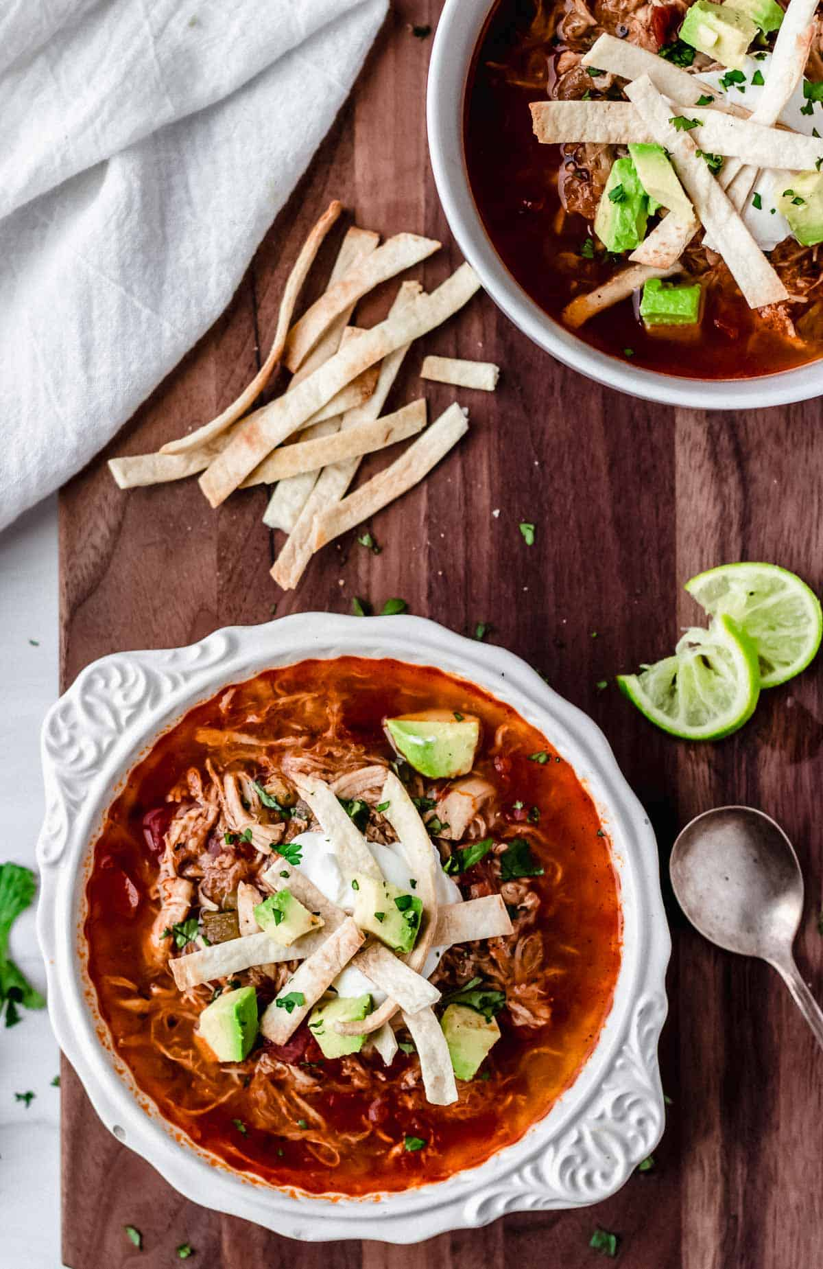 Overhead of two white bowls of Chicken Tortilla Soup on a wood board with a white napkin, tortilla strips, lime wedges, a spoon and a white towel