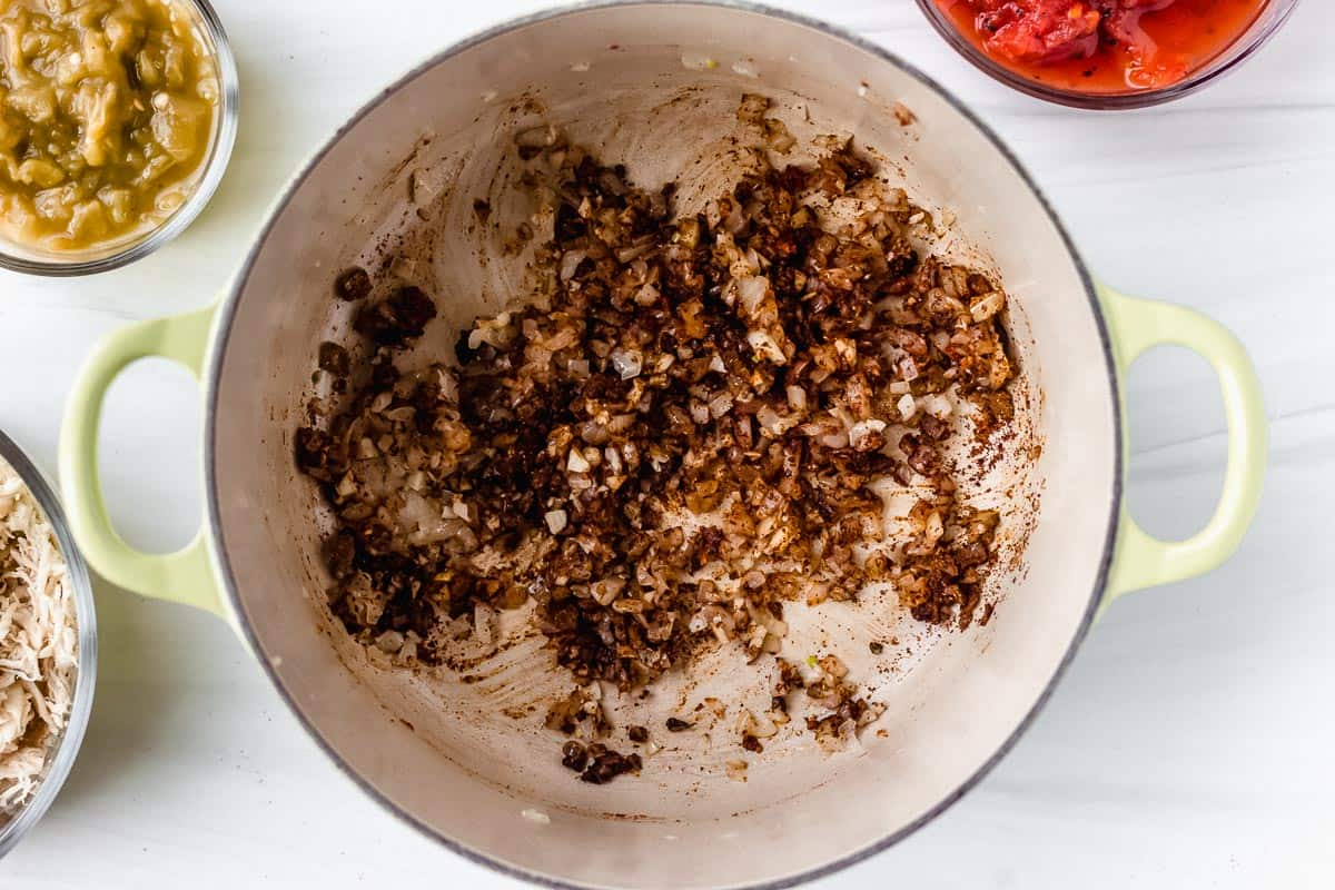 Onion, garlic and Mexican spices cooking in a Dutch oven over a white background with other ingredients around it