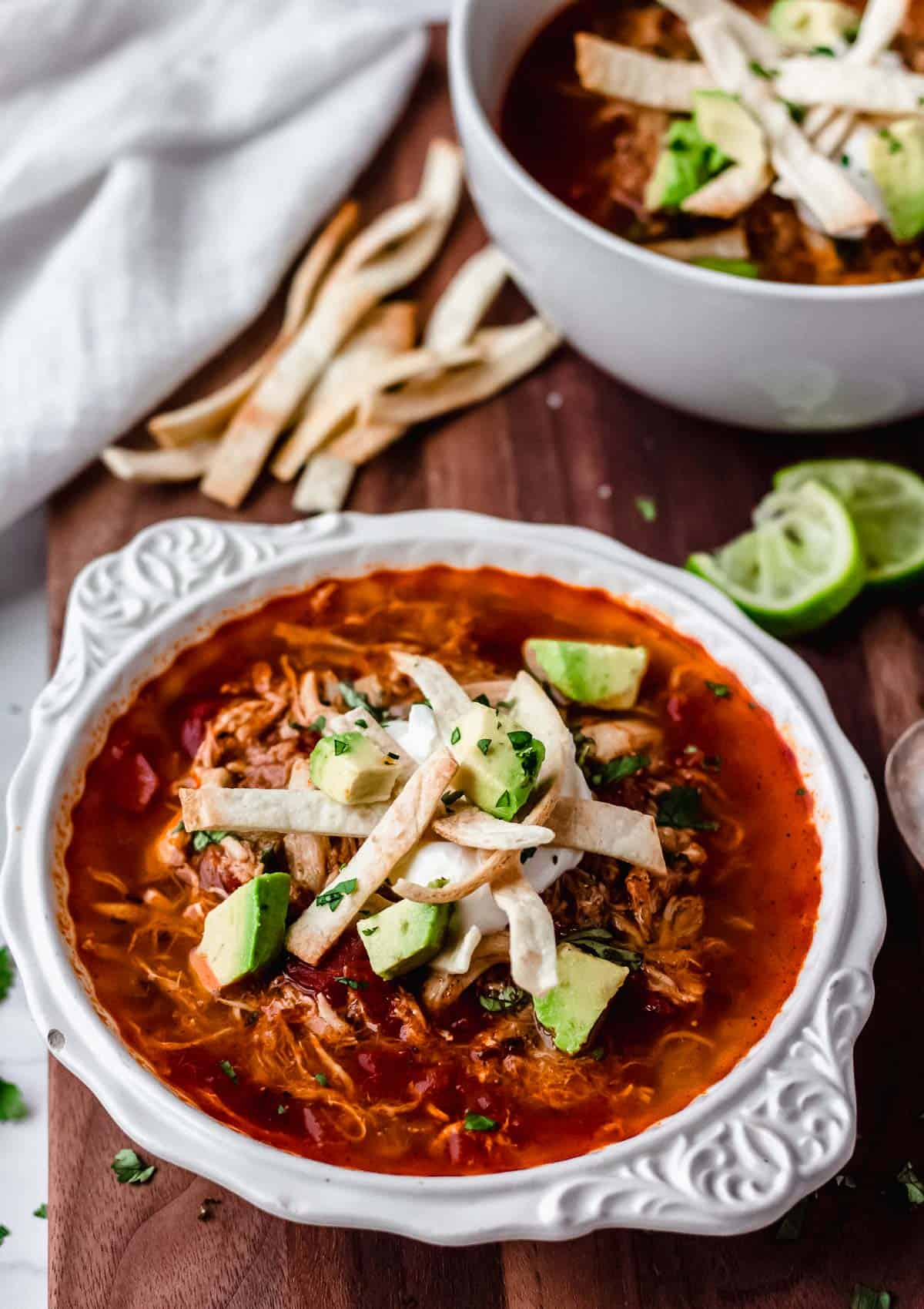 Keto Chicken Tortilla Soup in a white bowl on a wood board with lime wedges, tortilla strips, a white towel and part of a second white bowl with soup in the background