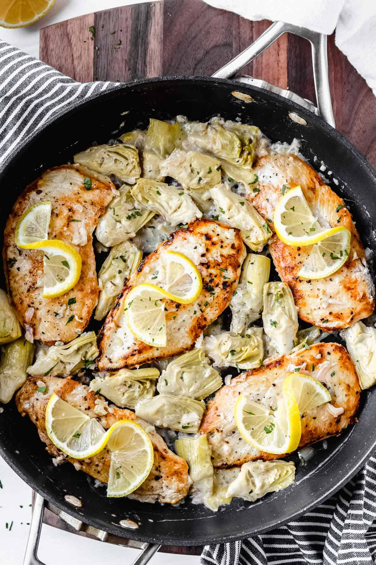 Overhead view of creamy lemon artichoke chicken in a black skillet over a wood board with a striped towel under it