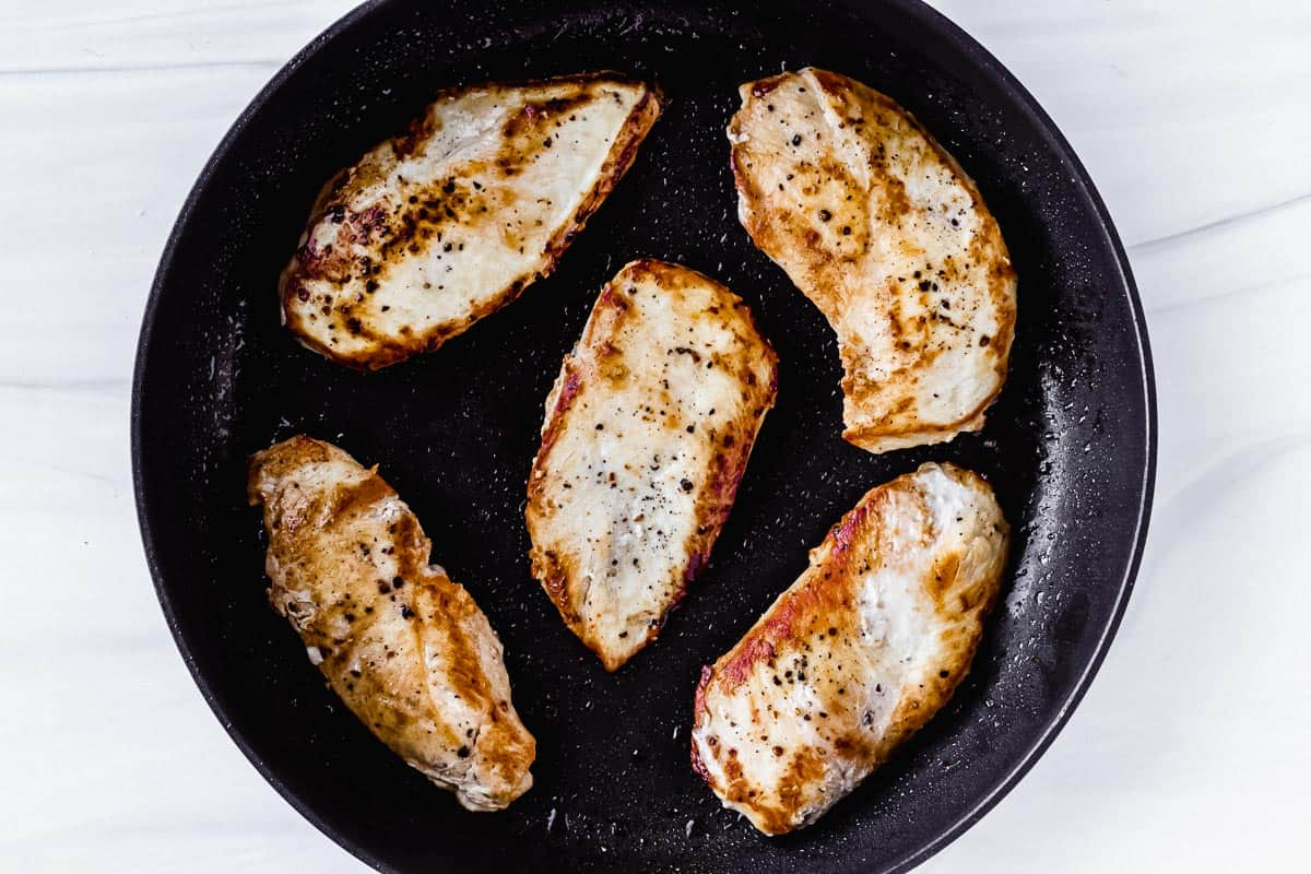 6 seared chicken breasts in a black skillet