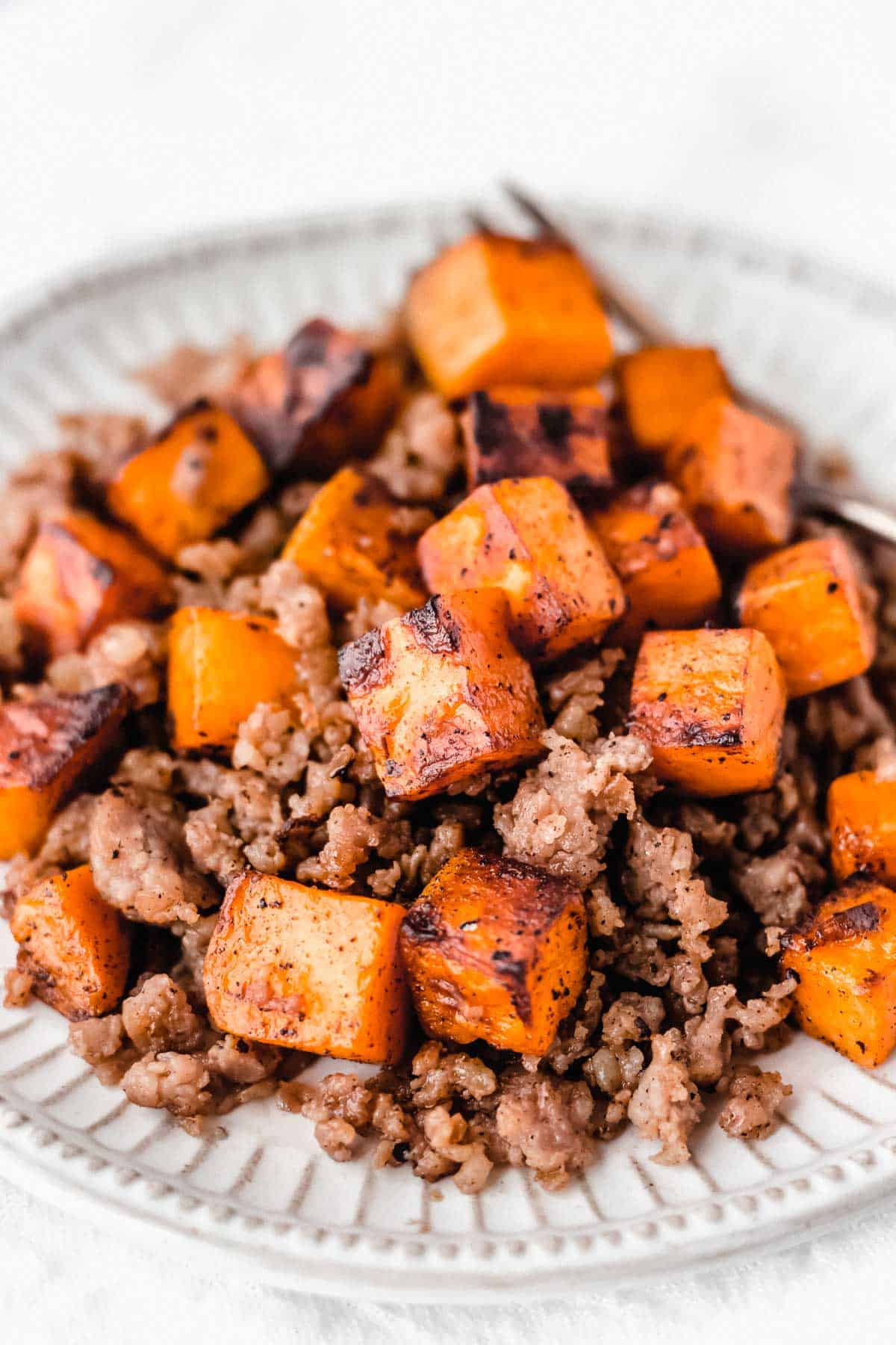 CLose up of maple sausage sweet potato hash on a white plate with a fork