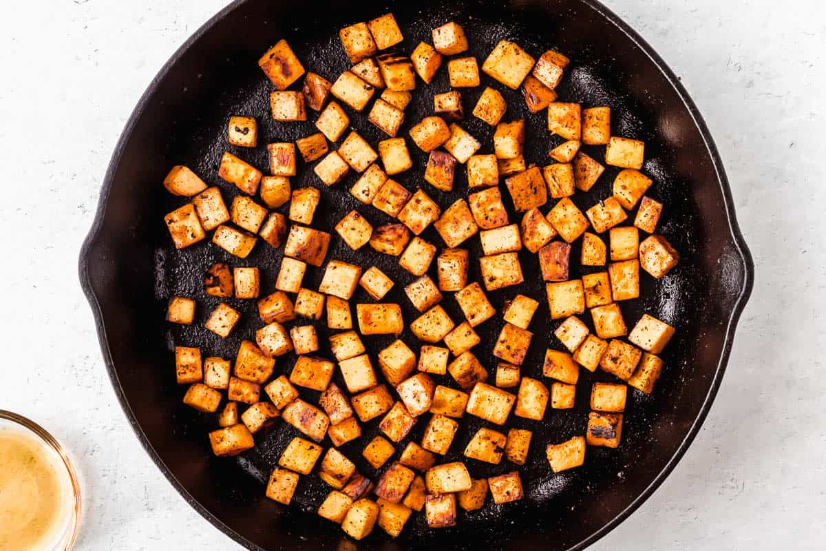 Cubes of sweet potatoes cooking in a black cast iron skillet