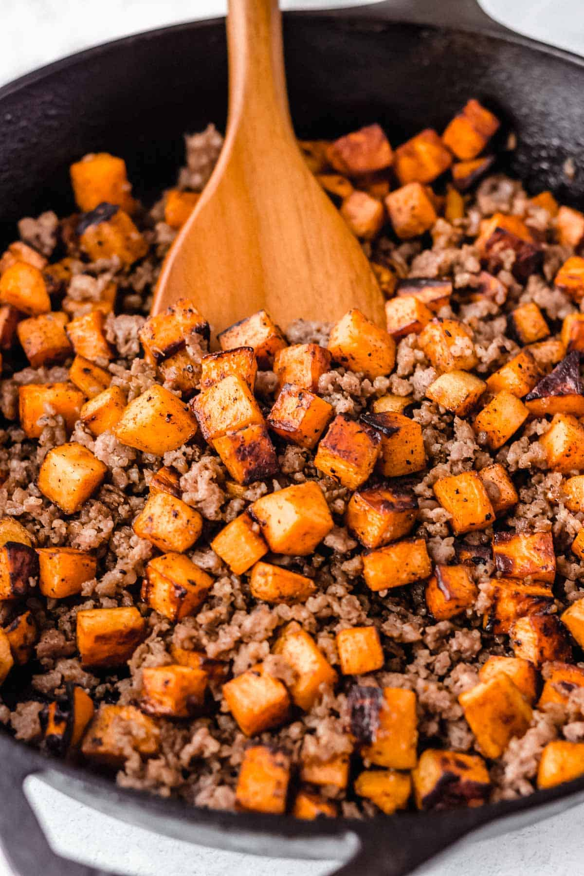 Cast iron pan full of maple sausage sweet potato hash with a wood server pushing up a scoop