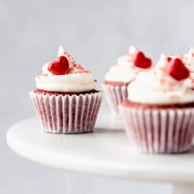 Mini Red Velvet Cupcakes on a white cake stand with a gray background