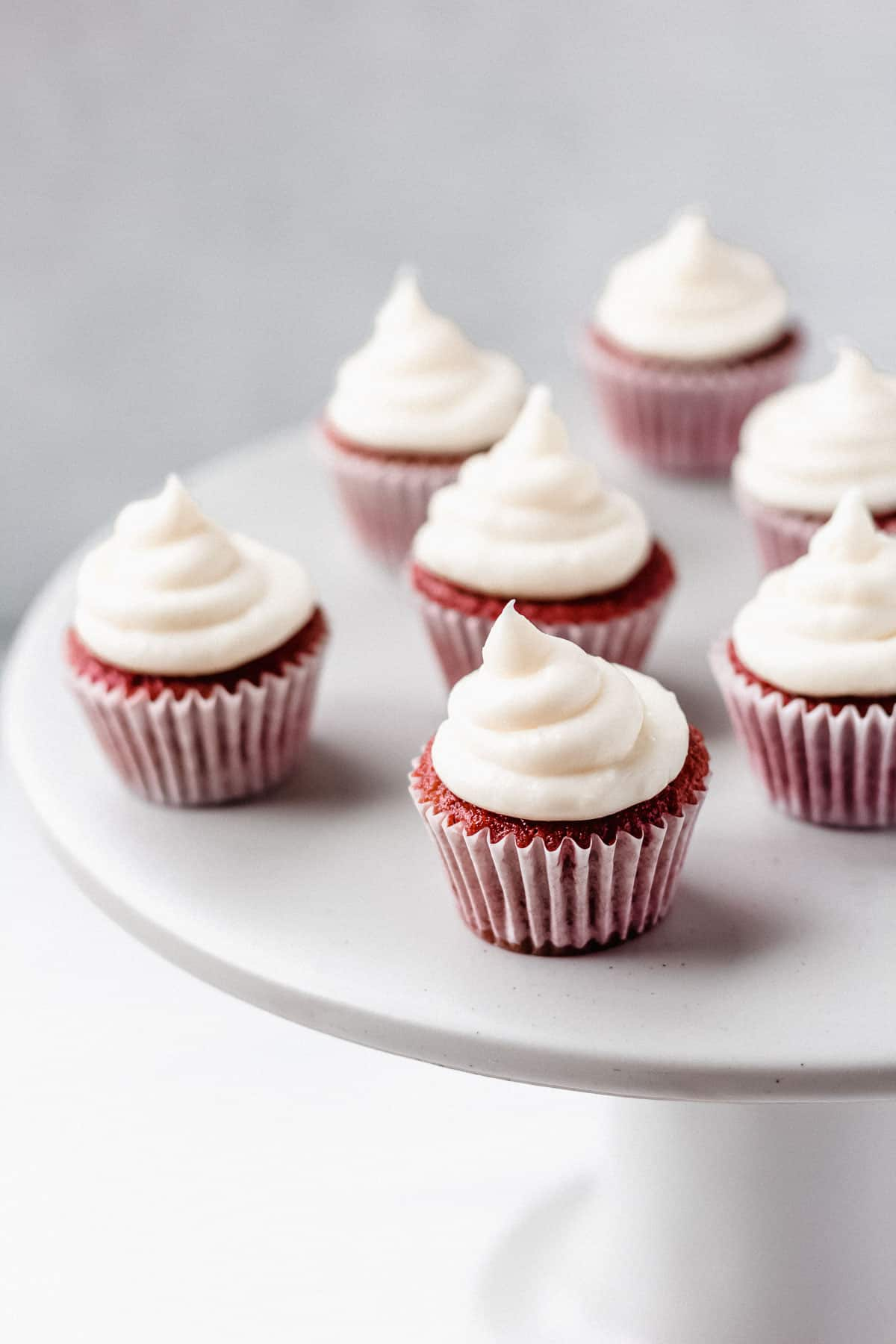 Mini red velvet cupcakes on a white cake stand with a gray and white background