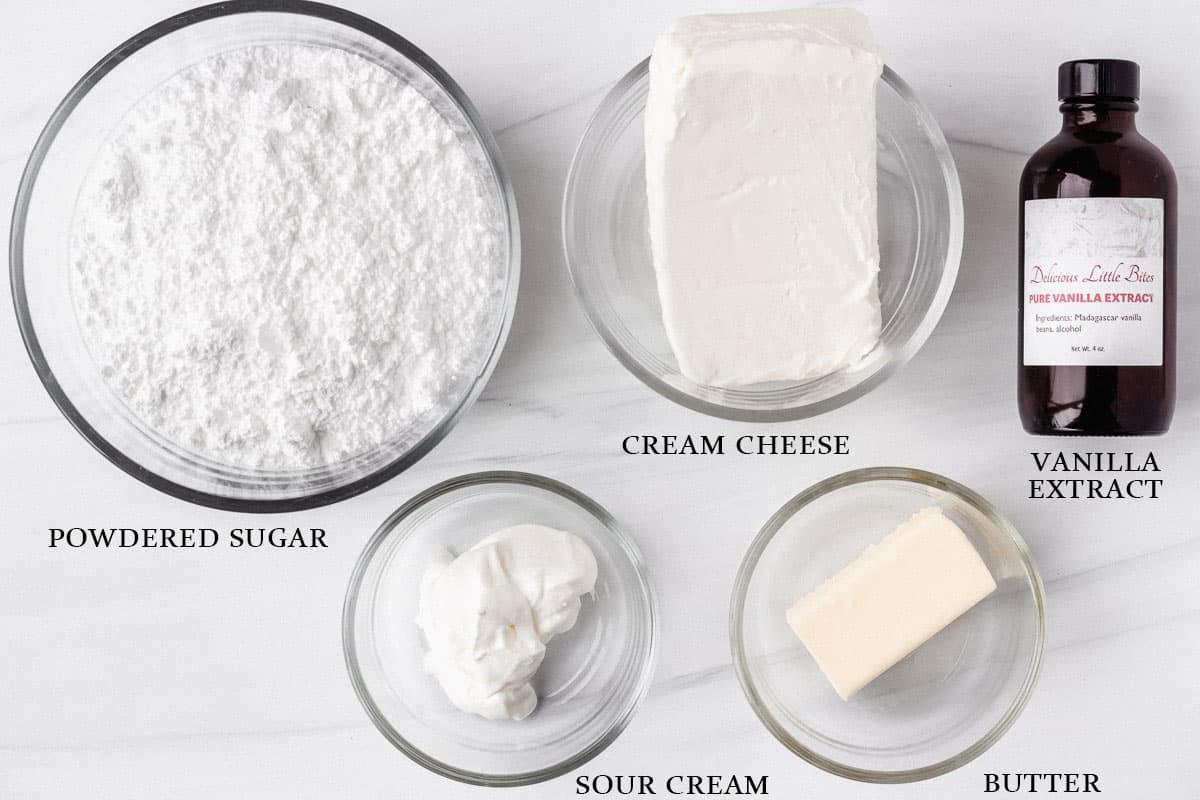 Ingredients to make vanilla cream cheese frosting on a white background with labels