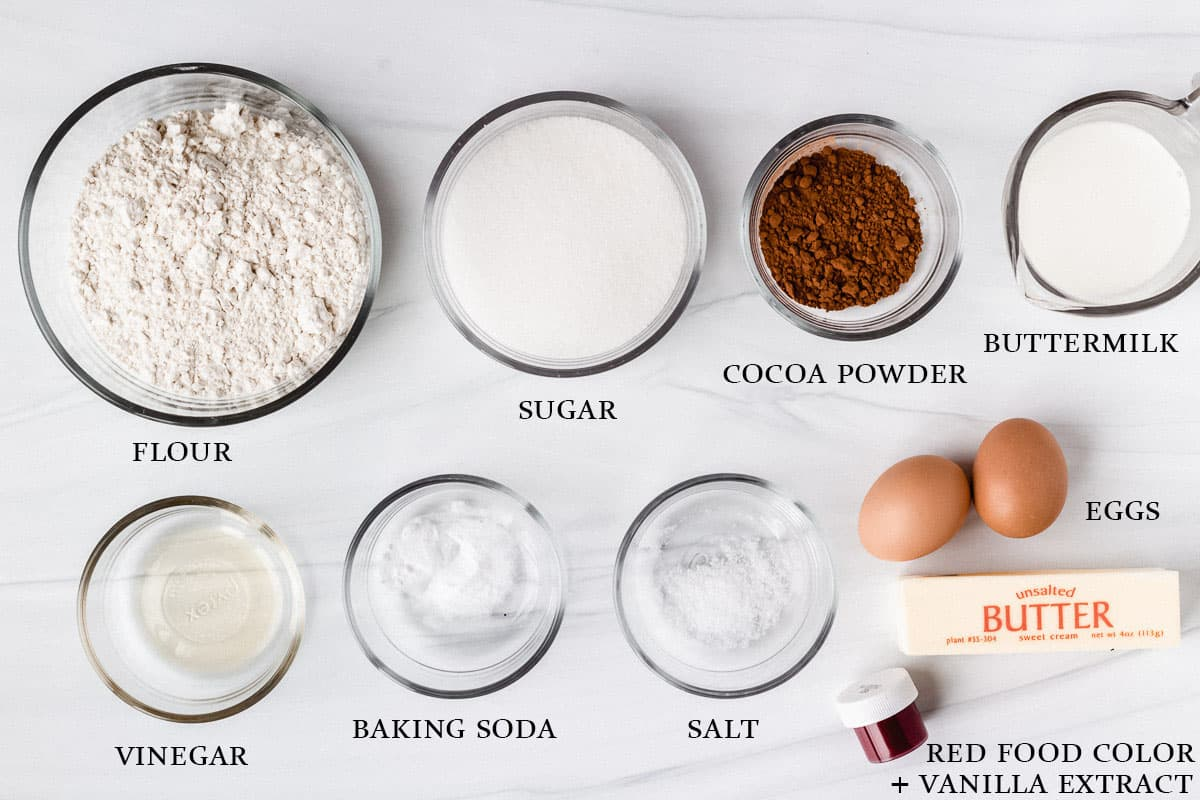 Ingredients to make red velvet cupcakes on a white background with labels