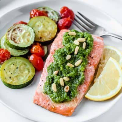 Baked Pesto Salmon on a white plate with lemon slices, zucchini and tomatoes