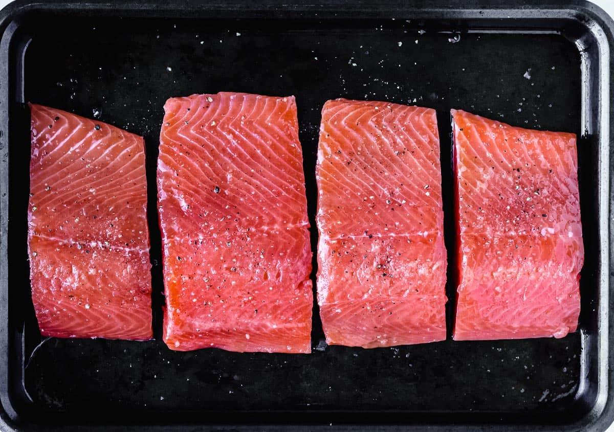 4 salmon fillets on a dark baking sheet