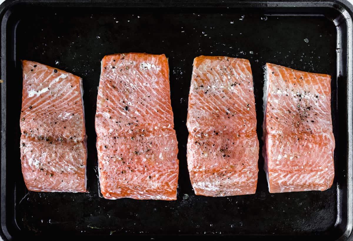 4 Baked Salmon fillets on a dark baking sheet