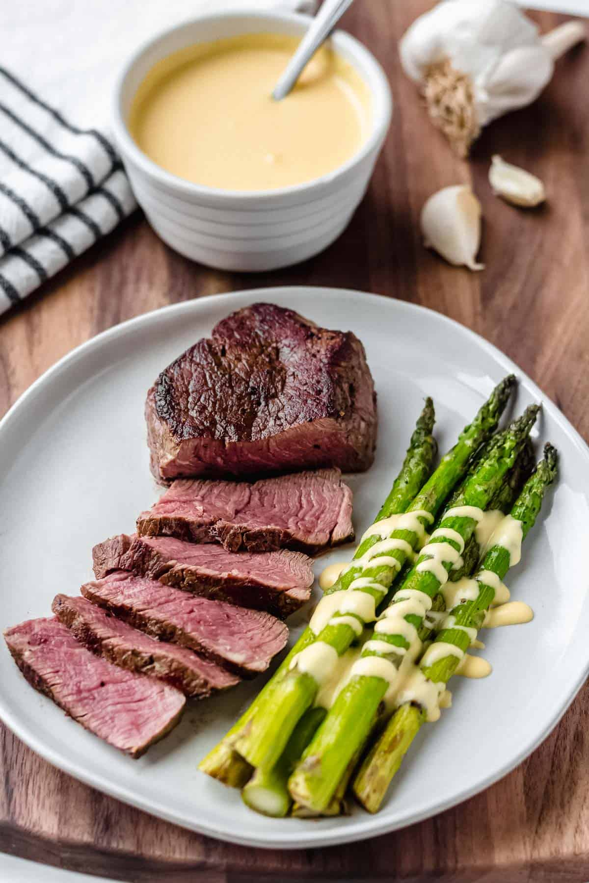 A plate with steak and asparagus drizzled with Hollandaise sauce on a wood background with garlic, a small bowl of hollandaise and a striped towel in the background