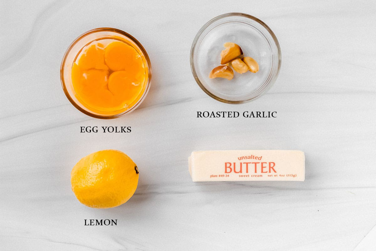 Ingredients to make roasted garlic hollandaise sauce on a white background with labels