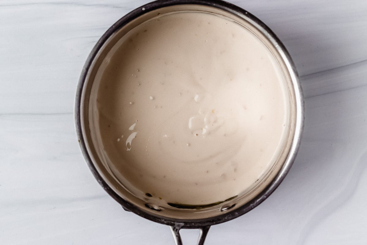 Alfredo sauce in a silver pot over a white background