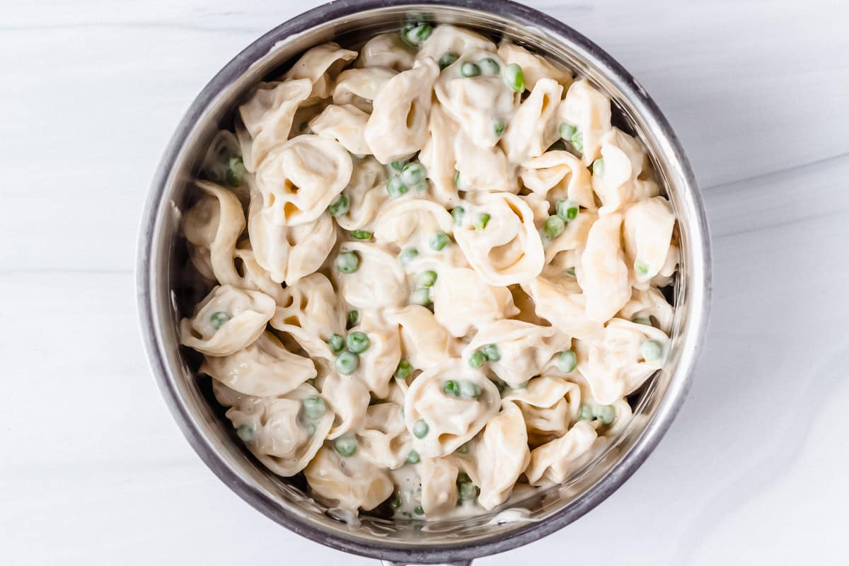 Tortellini alfredo with peas in a silver pot over a white background