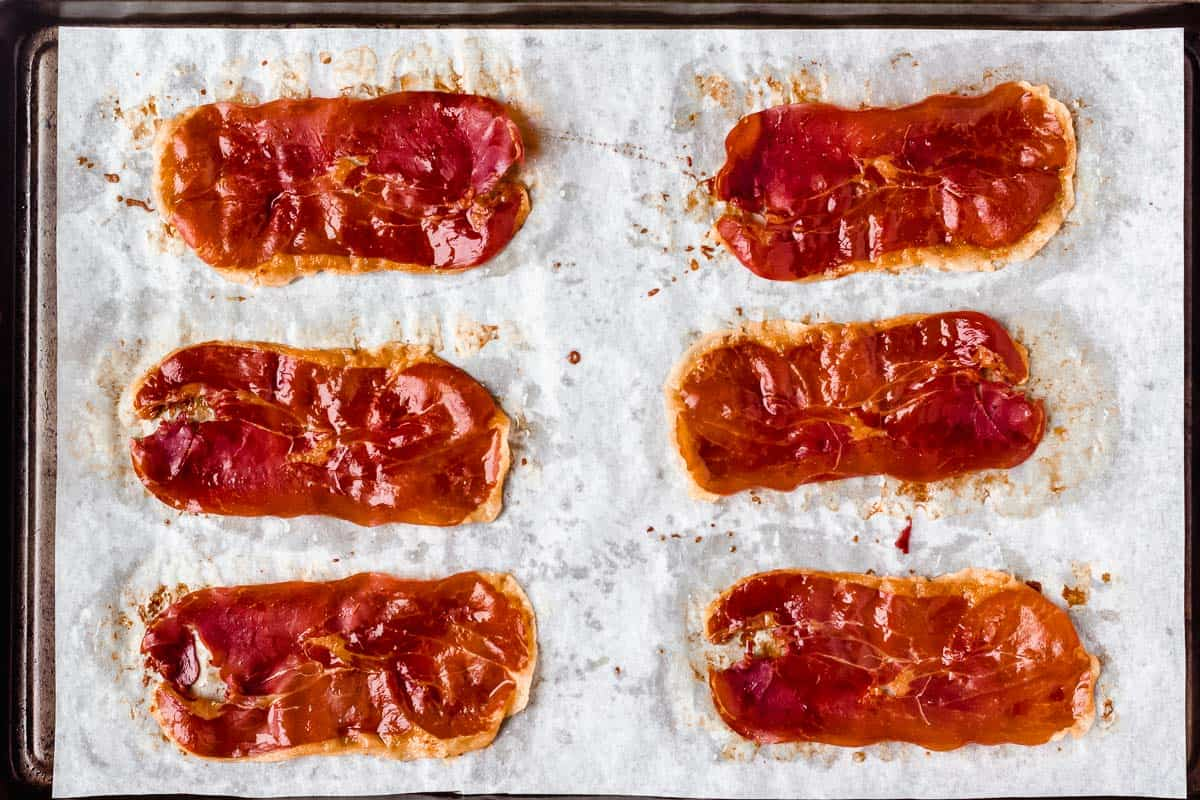 6 slices of crispy prosciutto on a parchment paper lined baking sheet