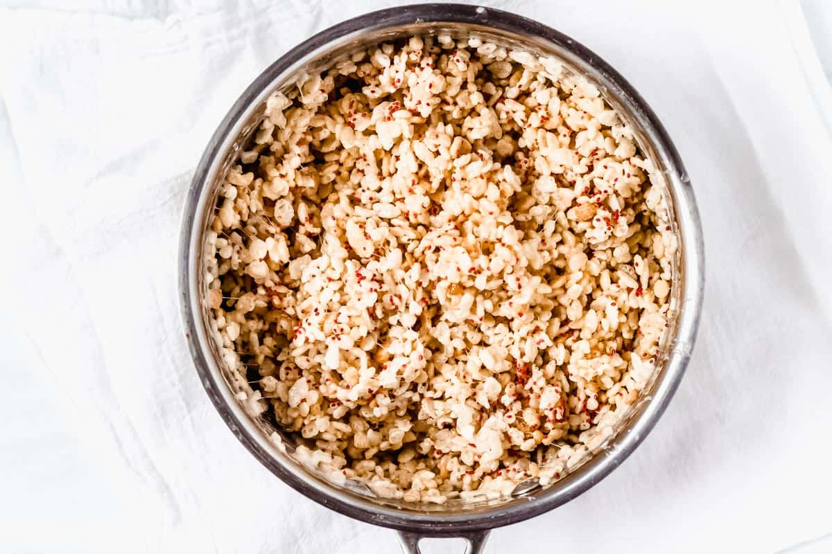 Rice cereal, marshmallows and cranberry seeds in a silver pot over a white background