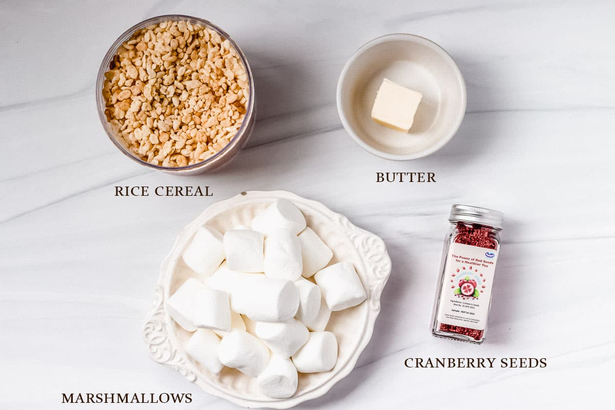 Ingredients to make crispy cereal treats with cranberries labeled on a white background
