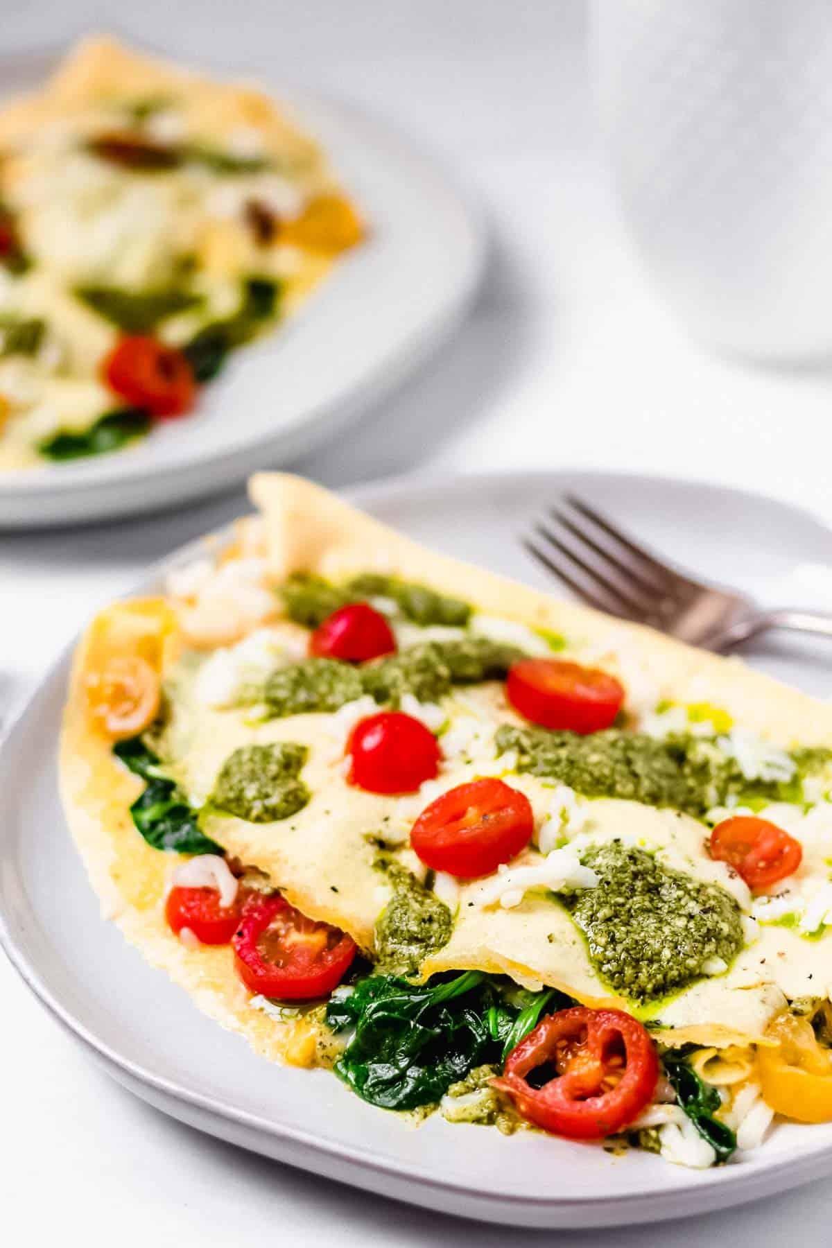 Pesto Caprese Omelet with Mozzarella Cheese and Cherry Tomatoes on white plates on a white backdrop