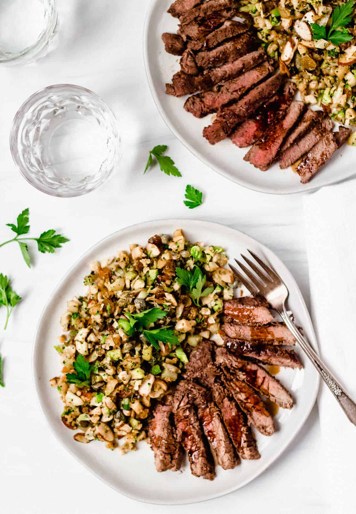 2 plates of steak and vegetables on white plates with 2 glasses of water and parsley on a white backdrop