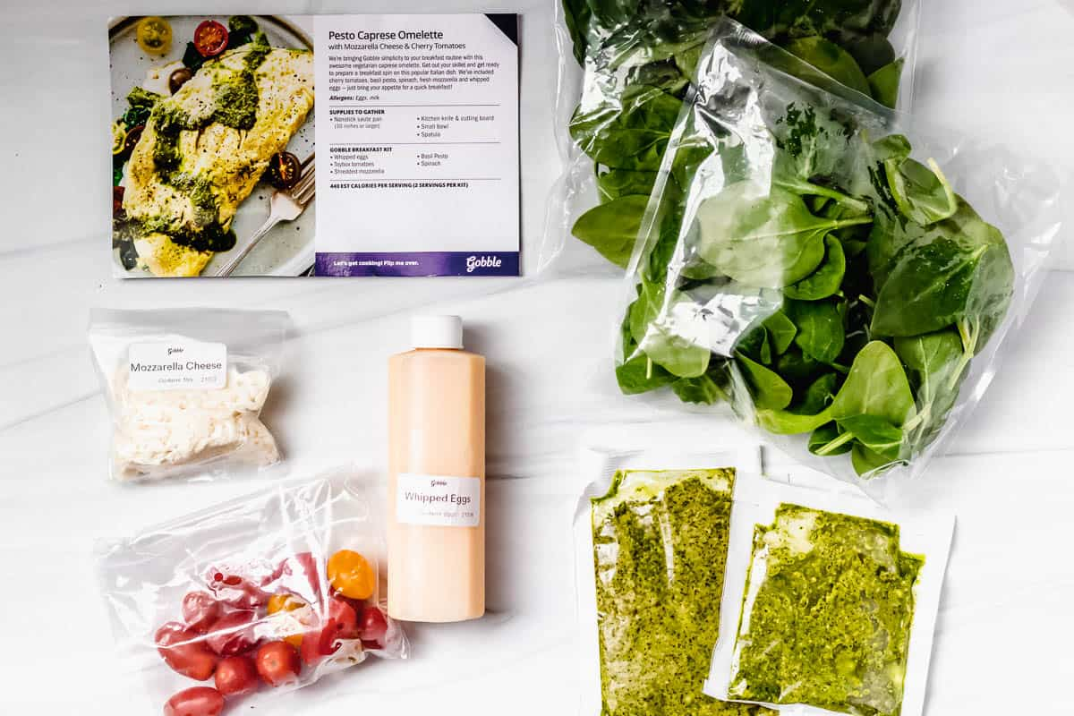 Ingredients to make pesto omelets laid out on a white background