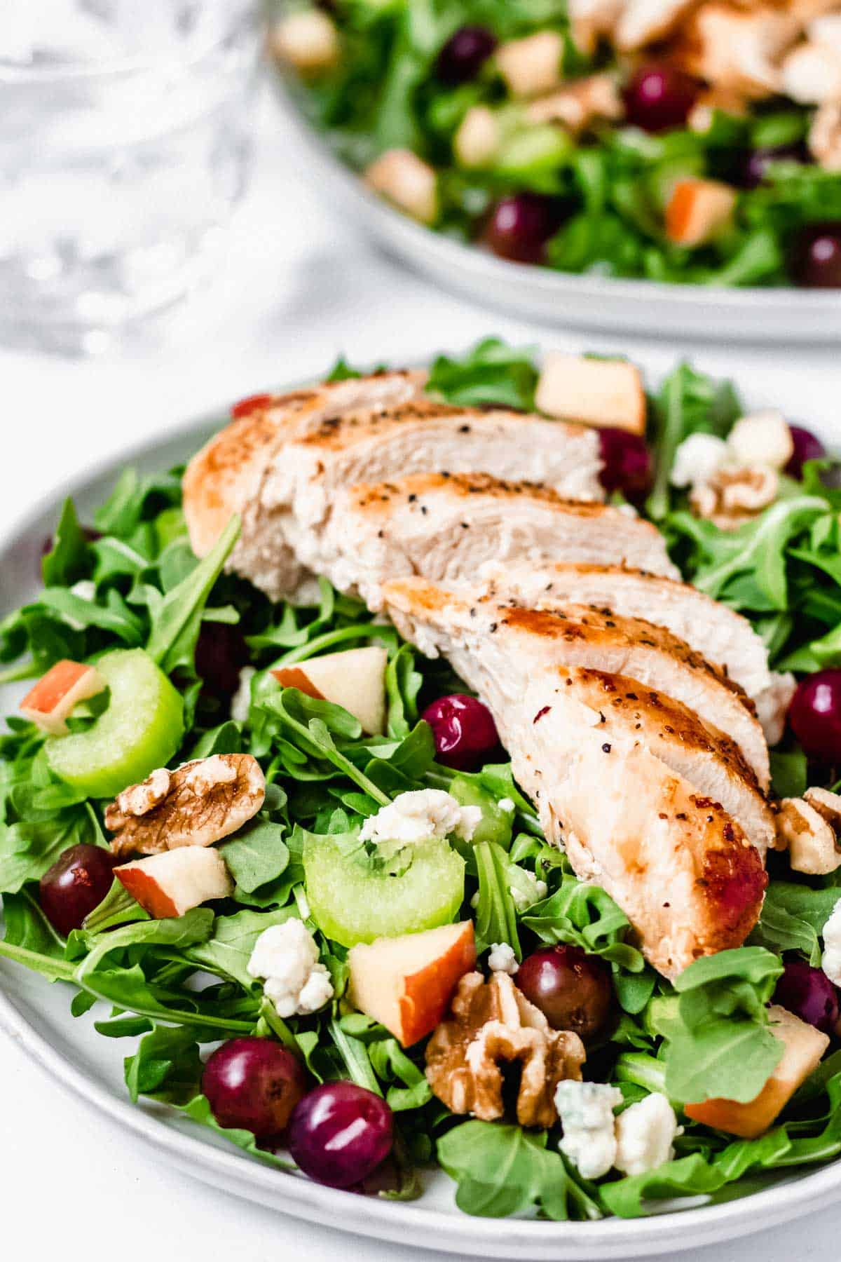 Waldorf salad with grilled chicken on two plates with a glass of water in the background on a white backdrop