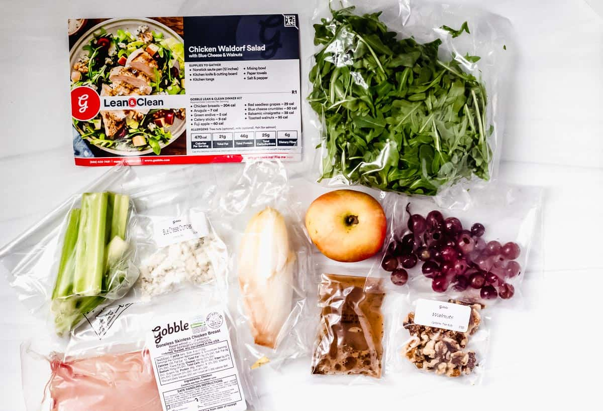 Waldorf salad ingredients laid out on a white backdrop