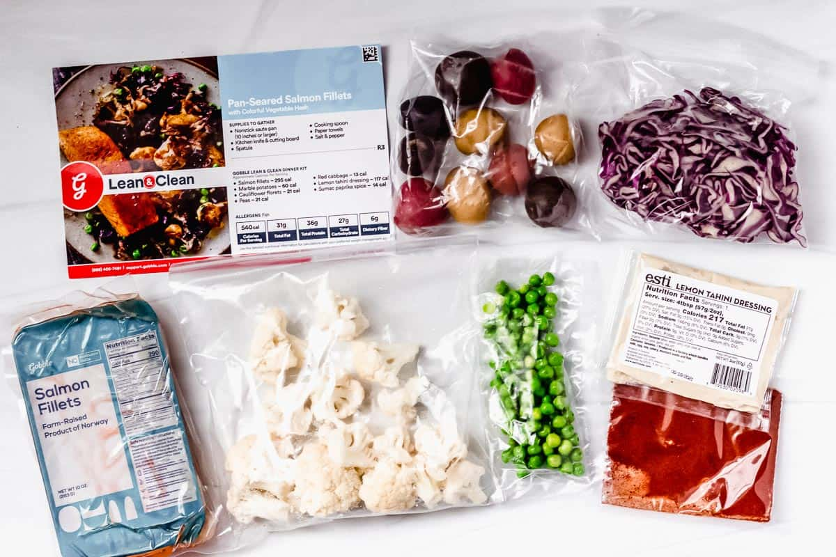Ingredients to make salmon and vegetable hash laid out on a white backdrop