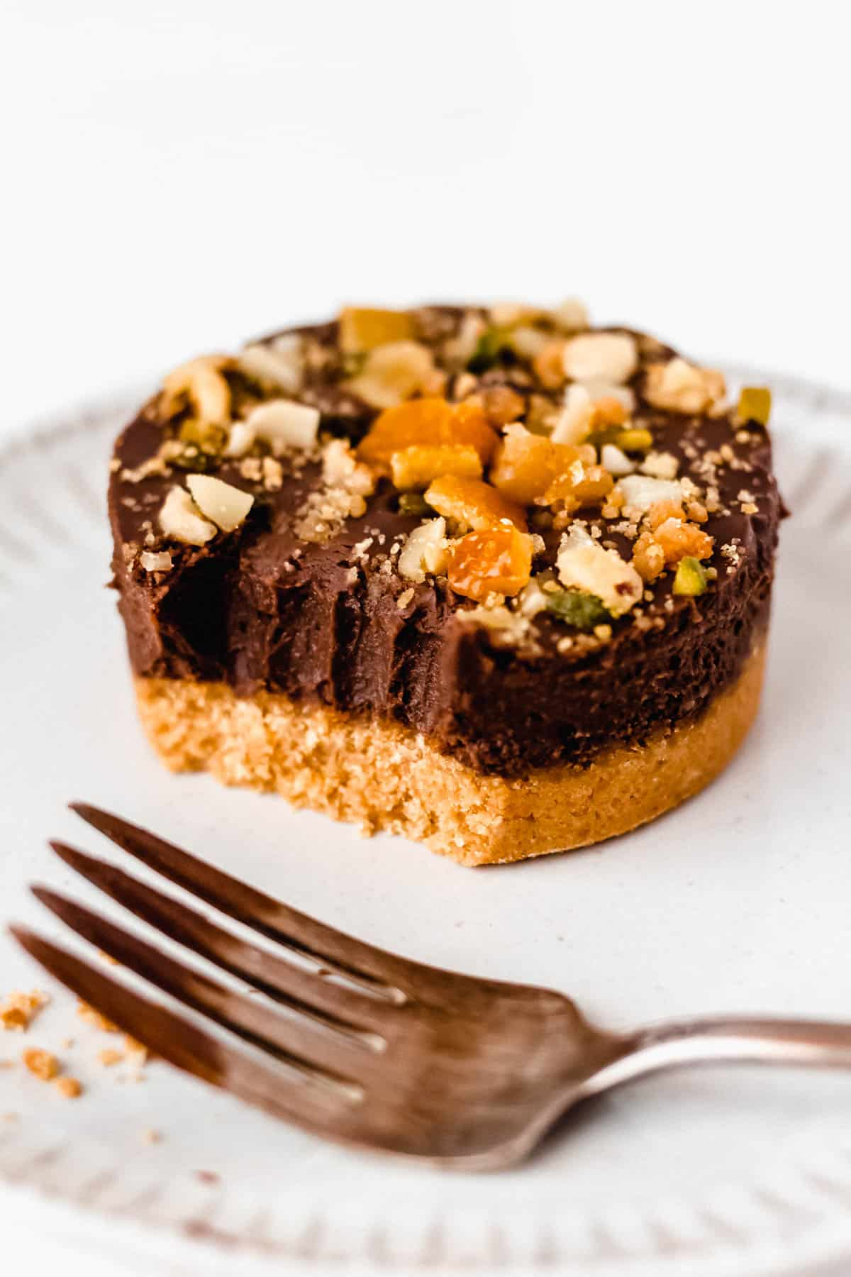 Hazelnut Gianduja Cake on a white plate with a bite taken out and a fork