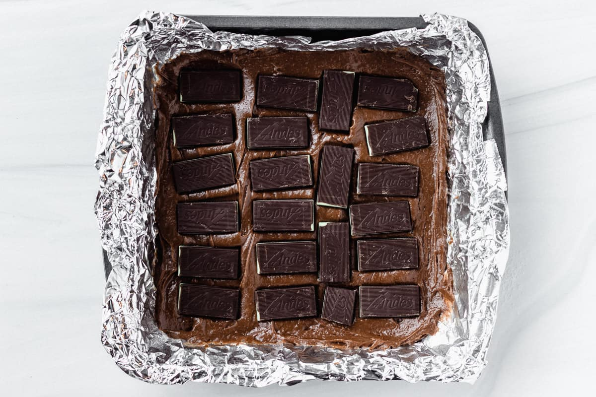 Half of a square pan of brownie batter topped with Andes candies over a white backdrop