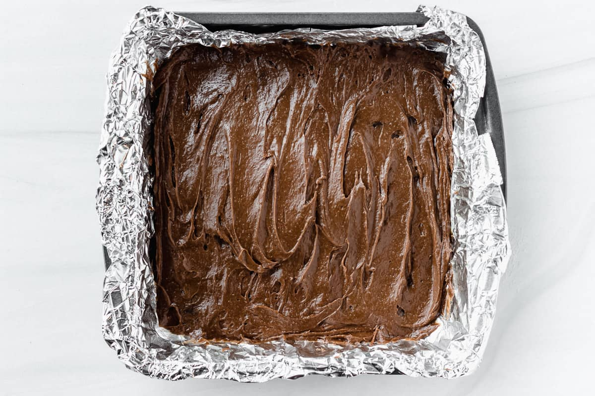 Brownie batter in a foil lined square pan over a white background