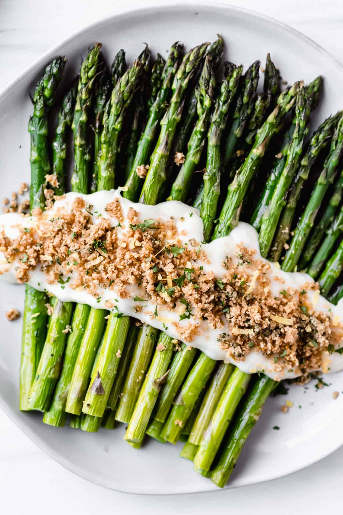 Overhead view of broiled asparagus with parmesan cheese sauce and almond flour crumbs on a white plate over a white background