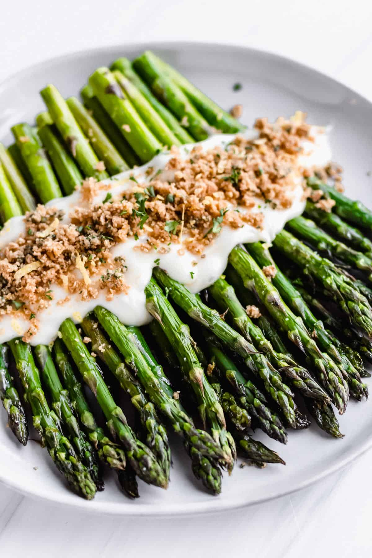 Broiled asparagus spears on a white plate topped with parmesan sauce and toasted almond flour bread crumbs
