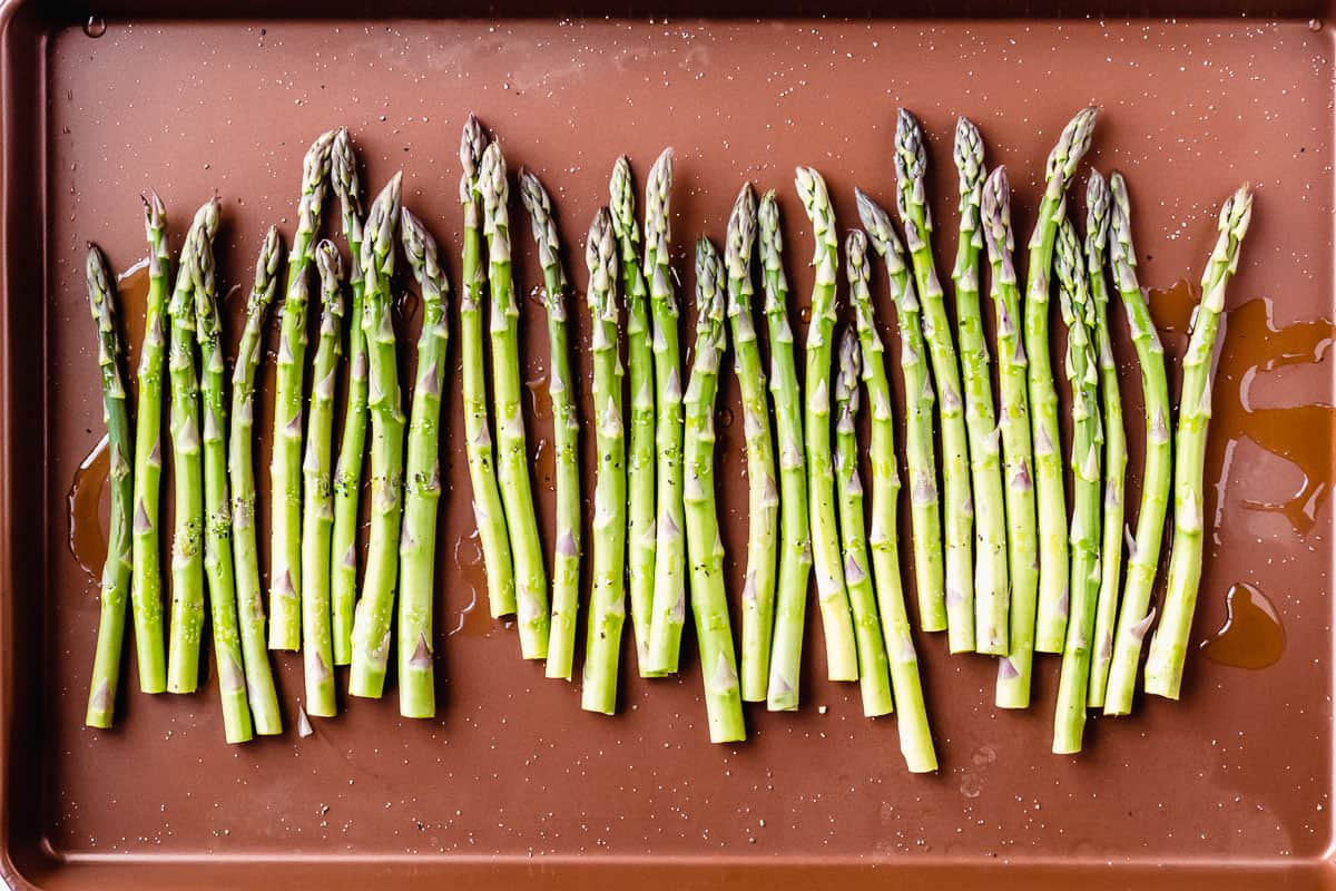 Raw asparagus drizzled with olive oil, salt and pepper on a copper baking sheet