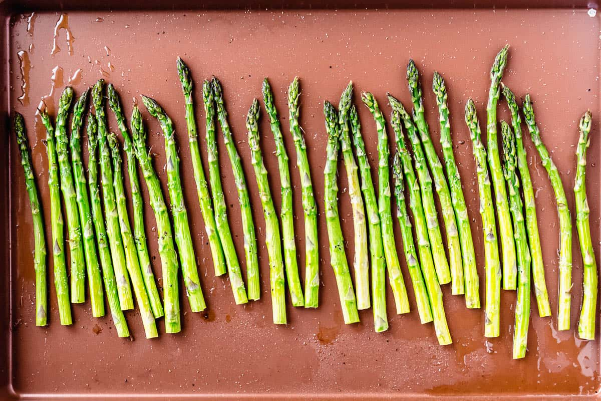 Broiled asparagus with salt and pepper on a copper sheet pan