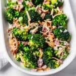 close up of half of a white oval serving tray filled with keto broccoli salad on a white backdrop