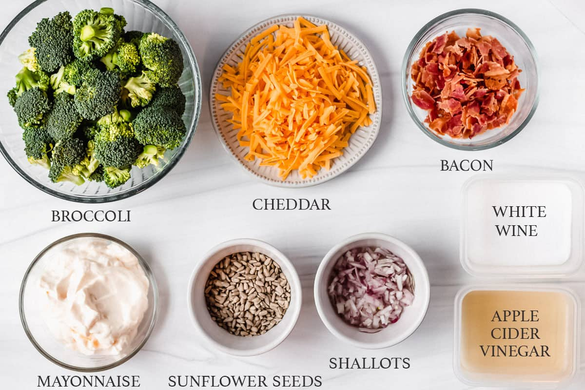 Ingredients to make keto broccoli salad on a white background with labels