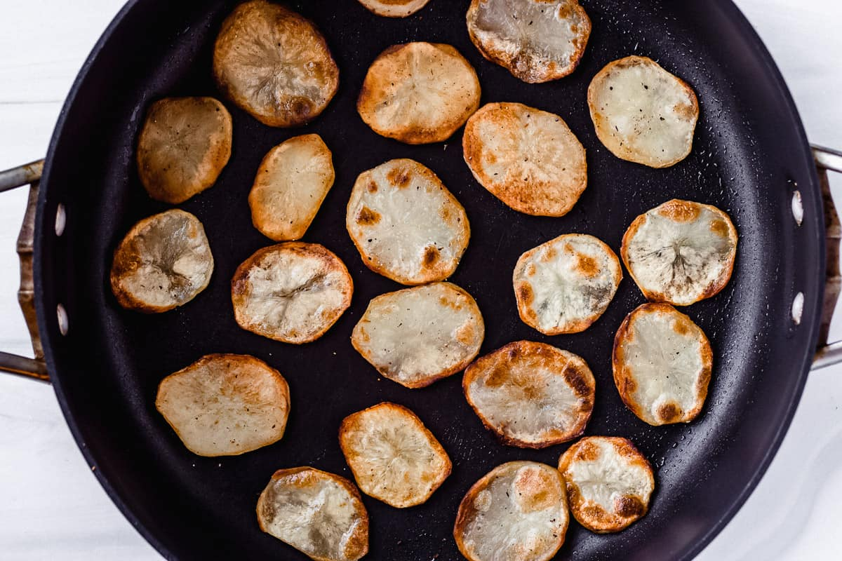 slices of fried potatoes in a black skillet