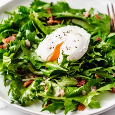 Lyonnaise salad with a poached egg cut open over the top on a white plate over a white background