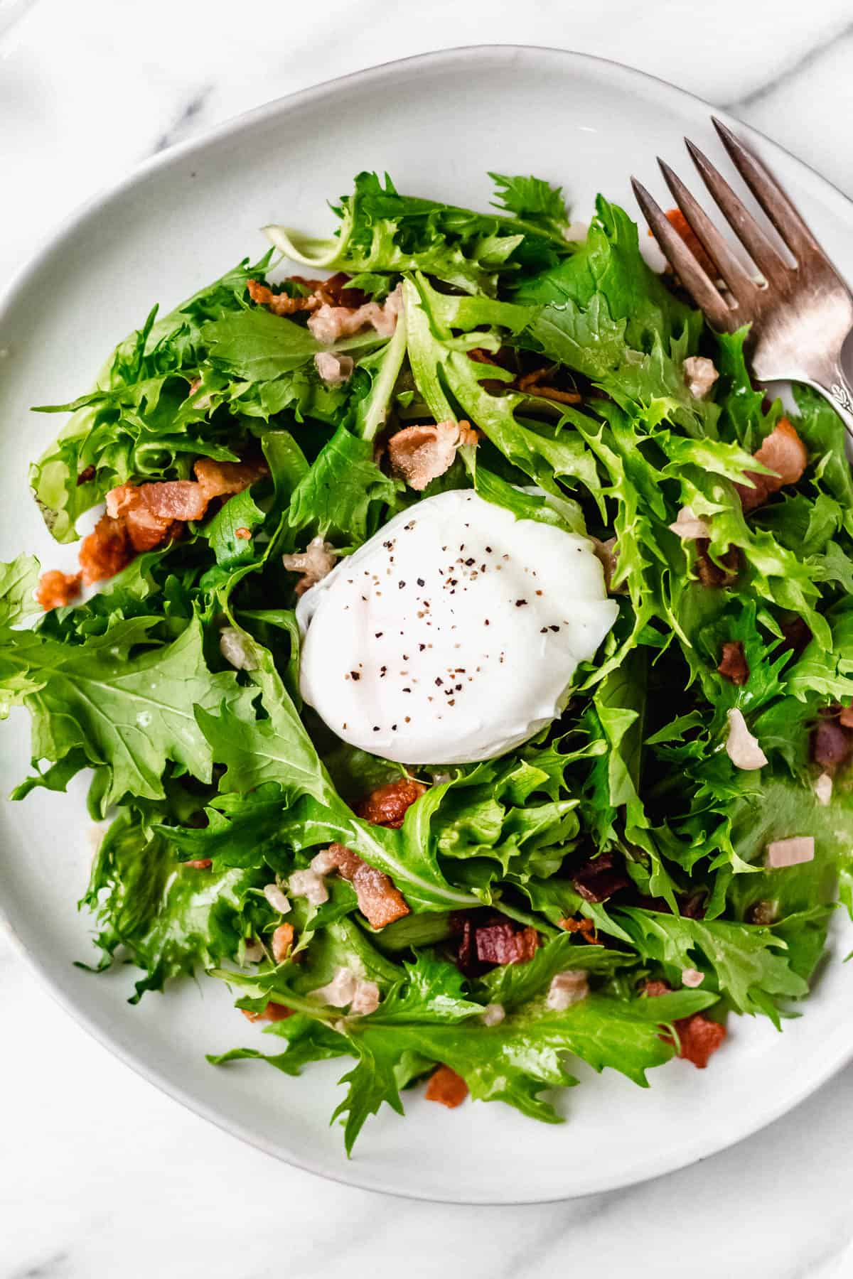 Overhead view of lyonnaise salad with an intact poached egg on top on a white plate with a fork