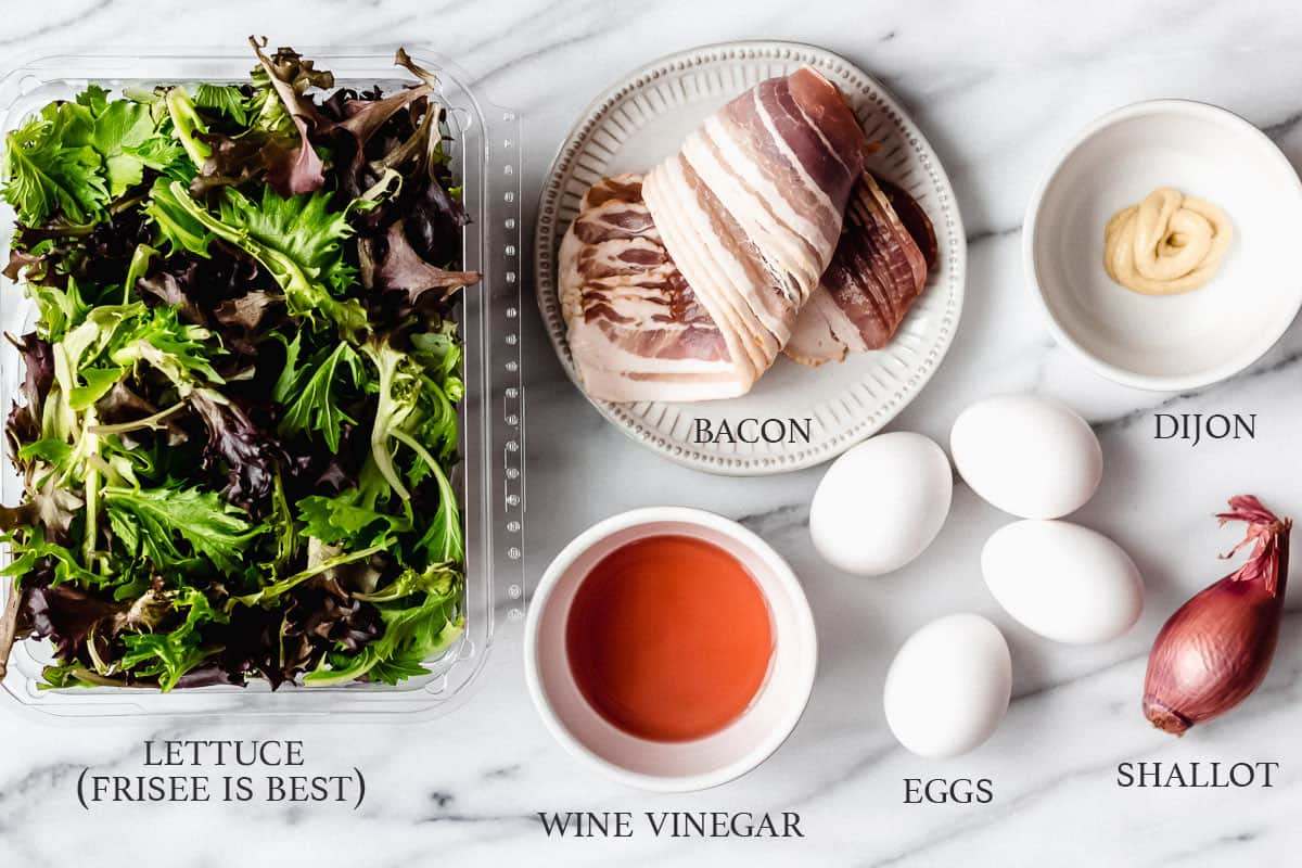 Ingredients needed to make lyonnaise salad on a white background with labels