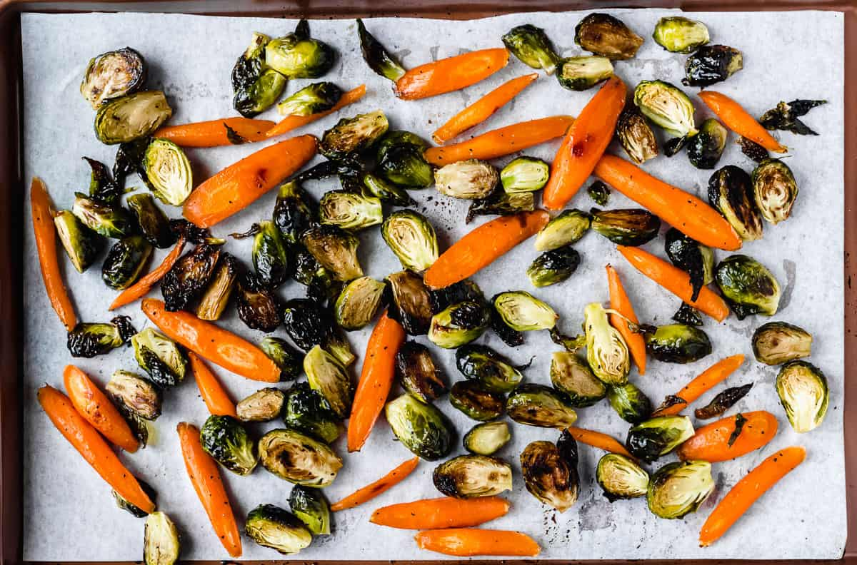 Roasted brussels sprouts and carrots on a parchment paper lined baking sheet