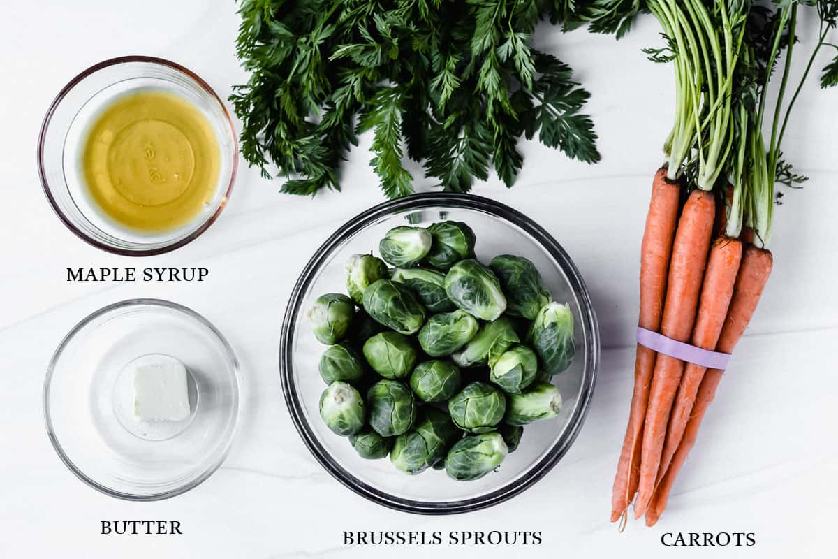 Ingredients to make maple roasted carrots and brussels sprouts on a white background with labels