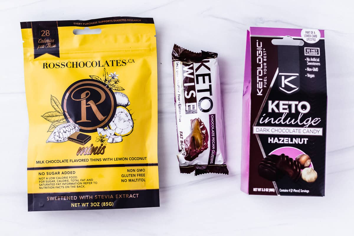 3 brands of keto chocolates on a white background